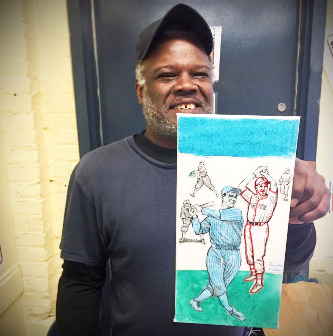 Artist Fausto Vizcaino holding a painting
